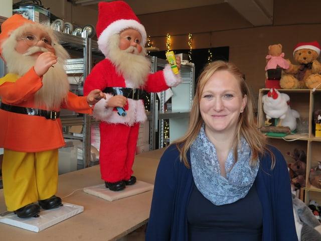Eine Frau steht vor mehreren Weihnachtsfiguren.