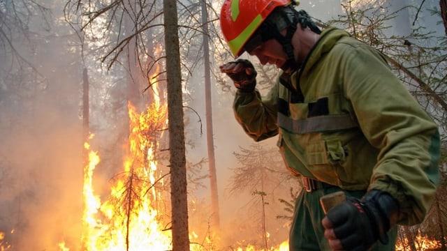 Feuerwehrmann steht im Wald neben den Flammen.