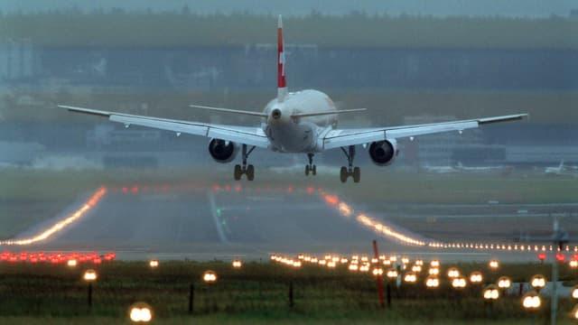 Flugzeug landet auf Piste bei Dämmerung