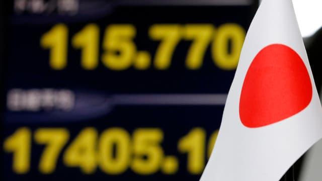 Eine japanische Flagge, im Hintergrund verschwommene Zahlen auf einer Anzeigetafel.