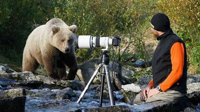 Der Schweizer Bärenforscher David Bittner und ein Bär in einem Bachbett in Alaska.
