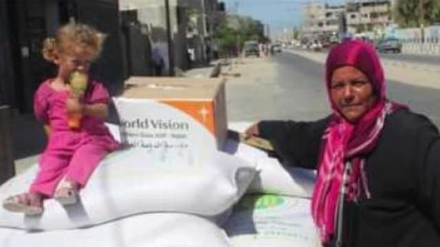 Ein Mädchen sitzt auf weissen Lebensmittelsäcken vor einer Schachtel mit dem World-Vision-Logo, daneben steht eine Frau mit Kopftuch.