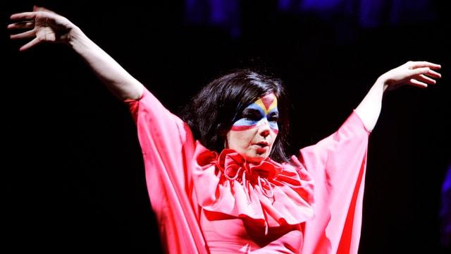 Björk in einem weite roten Umhang und bunt geschminkte Gescicht auf einer Bühne.