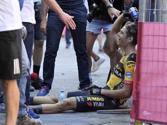 Wout van Aert nach seinem Sieg erschöpft auf dem Boden.
