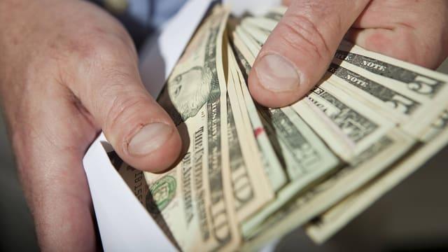Hände holen Dollar aus Umschlag.