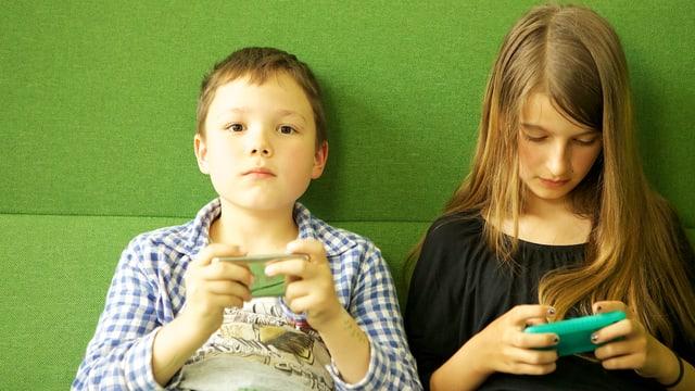 Zwei Kinder spielen mit Iphones.