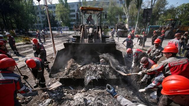 Arbeiter räumen mit Hilfe von Baumaschinen Barrikaden weg.