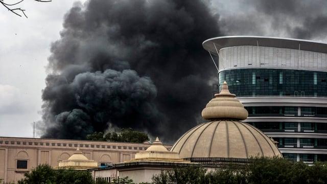 Ein Rauchsäule steigt hinter den Dächern von Gebäuden auf.