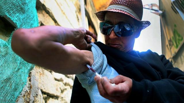Ein Mann setzt eine Spritze an seinem Arm an.