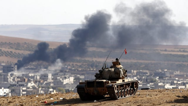 Ein türkischer Panzer auf einer Anhöhe nahe der Grenzstadt Kobane, wo Rauch aufsteigt.