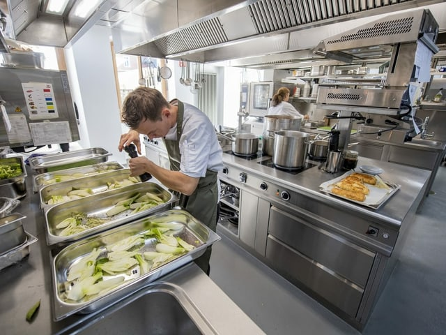 Ein Koch bereitet in der Küche im Culinarium Alpinum Essen vor