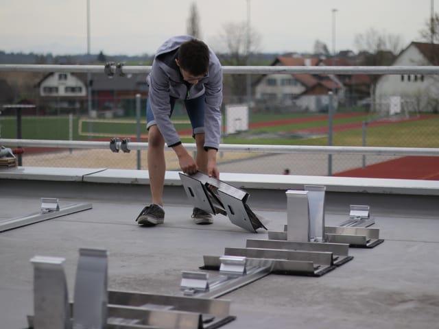 Ein Jugendlicher baut die Halterung für die Solarpanels auf dem Dach des Schulhauses auf.