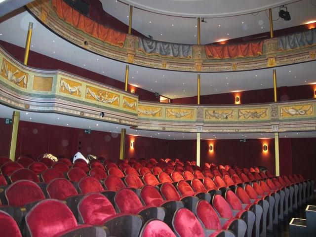 Theatersaal mit roten Stühlen.