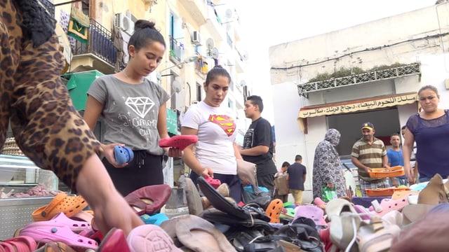 Frauen schauen Schuhe an auf einem Markt in Tunis.