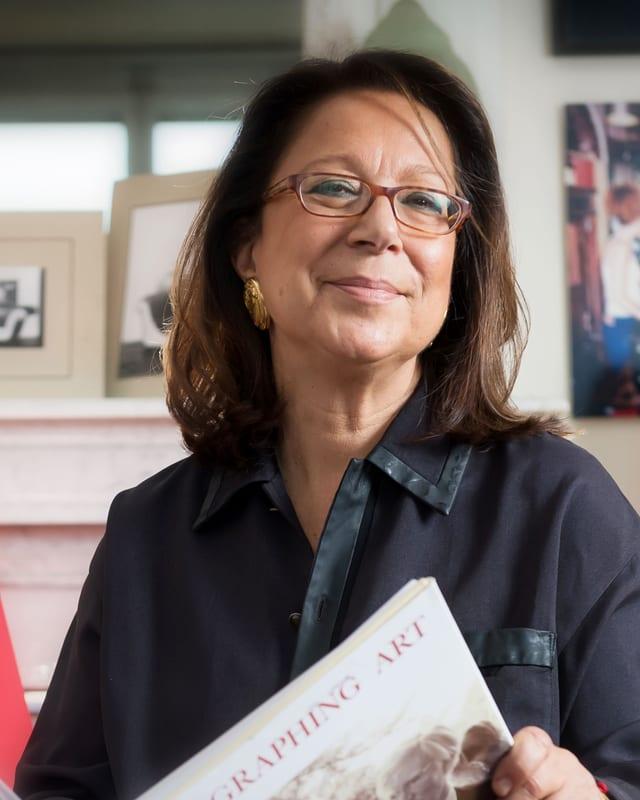 Adelina von Fürstenberg, ein Kunstkatalog in der Hand, lächelnd in die Kamera schauend.