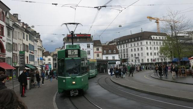 Barfüsserplatz mit wartenden Menschen und auf beiden Seiten der Tramstation ein Tram.