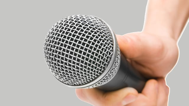Mann hält Mikrofon in der Hand
