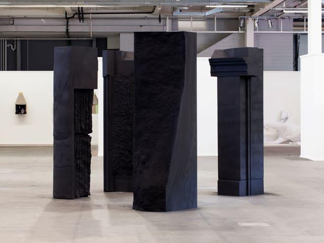 Vier grosse Säulen stehen in einem Raum.