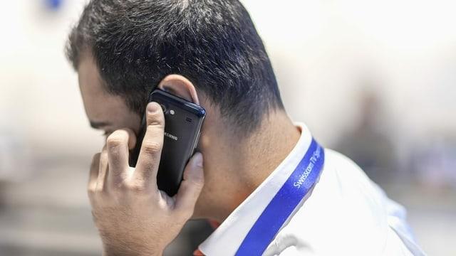 Vendader da Swisscom cun telefonin vi da l'ureglia.