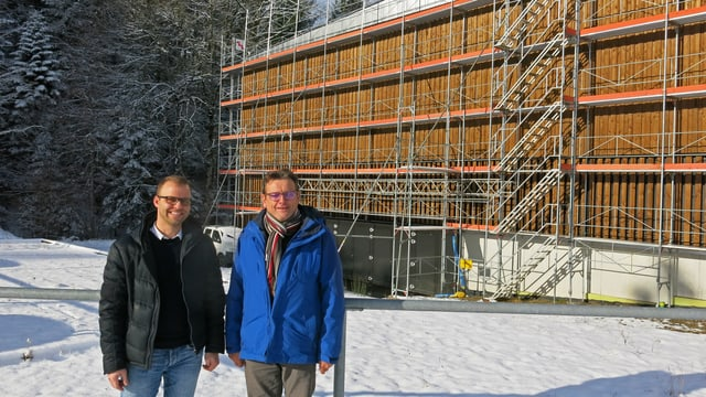 Zwei Männer stehen vor einer grossen Halle.