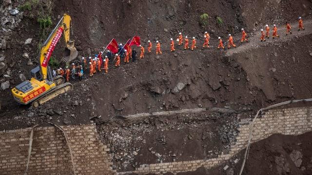 Rettungskräfte in oranger Kleidung und ein gelber Bagger an einem steilen Hang.
