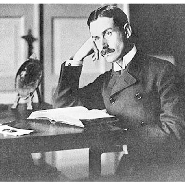 Thomas Mann sitzt über einem Buch am Schreibtisch.