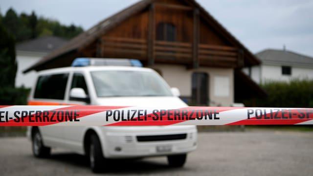 Absperrband und Polizeiauto vor Holzhaus