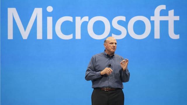 Steve Ballmer steht vor einem blauen Hintergrund auf dem Microsoft steht.