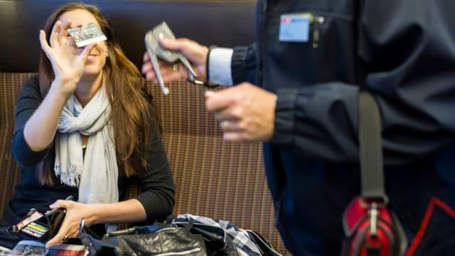 Eine Frau zeigt einem Zugkontrolleur ihren Fahrausweis