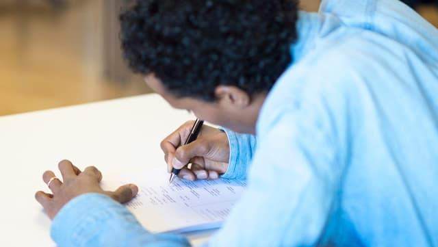 Ein Mann aus dem Ausland arbeitet an einer Schularbeit.