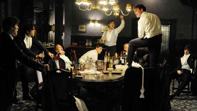 Bild aus dem Film Riot Club, Studenten besoffen auf dem Tisch