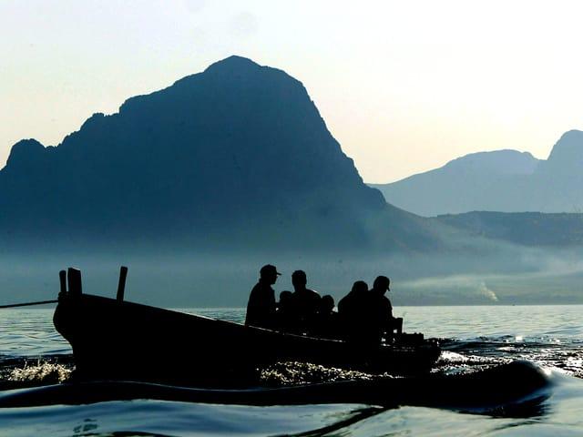 Ein Fischerboot auf dem Meer, im Hintergrund die Berge von Sizilien.