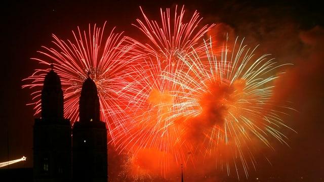 Die Silhouette des Grossmünsters vor dem Hintergrund gewaltigen roten Feuerwerks