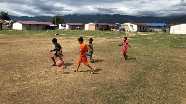 Kinder spielen Fussball in einem Barackenlager in Palu.