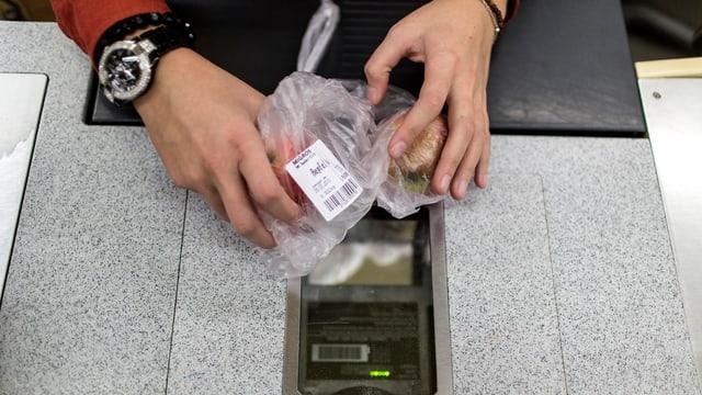 Eine Kassierer schiebt einen durchsichtigen Plastiksack über den Scanner an der Kasse.