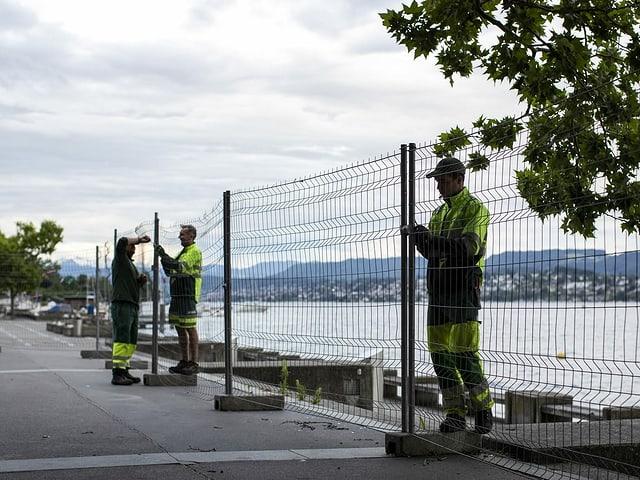 Mitarbeiter der Stadt entfernen die Absperrgitter rund um das Zürcher Seebecken.