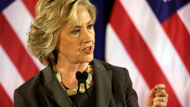 Hillary Clinton bei einer Rede vor einer US-Flagge.