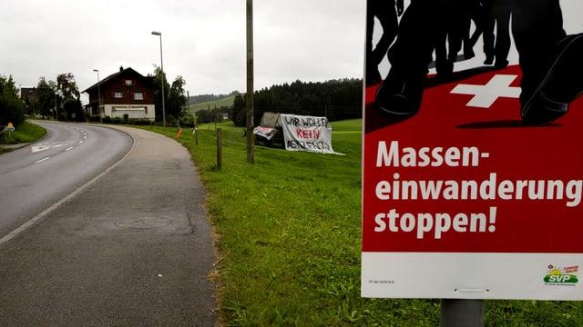 """Das Plakat """"Masseneinwanderung stoppen"""" steht an einem Strassenrand."""