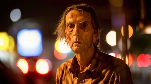 Ein alter, hagerer Mann schaut direkt in die Kamera. Im Hintergrund sieht man unscharf die nächtlichen Lichter einer Stadt.