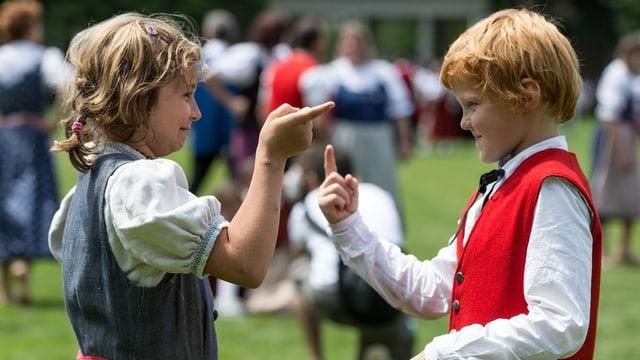 Ein Mädchen und ein Knabe, beide in Tracht gekleidet, flirten beim Tanzen.