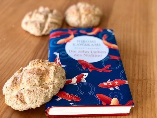 Der  Roman «Die zehn Lieben von Nishino» von Hiromi Kawakami liegt auf einem Tisch, angelehnt am Buch ein japanisches  Melonpan - ein weiche Biskquitkugel.