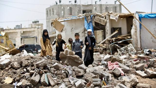 Kinder stehen auf einem Schutthügel vor einem zerbombten Haus.
