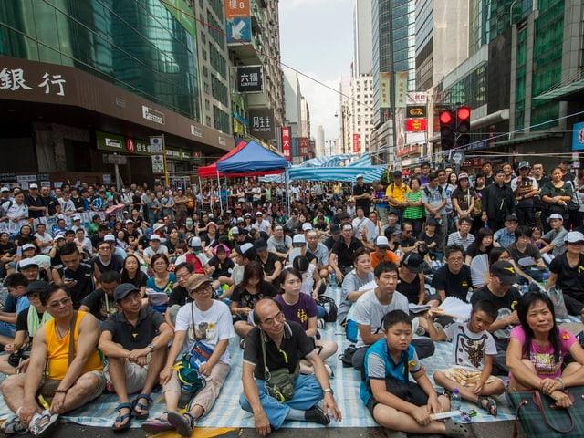 Menschen blockieren sitzend eine Strasse