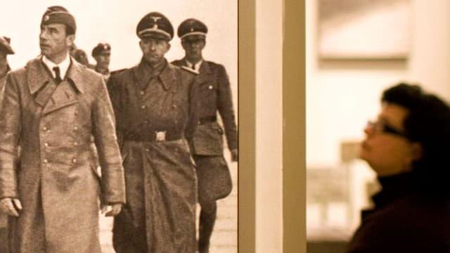 Am linken Bildrand Soldaten aus dem zweiten Weltkrieg auf einem Foto, rechts eine Betrachterin der Szene.