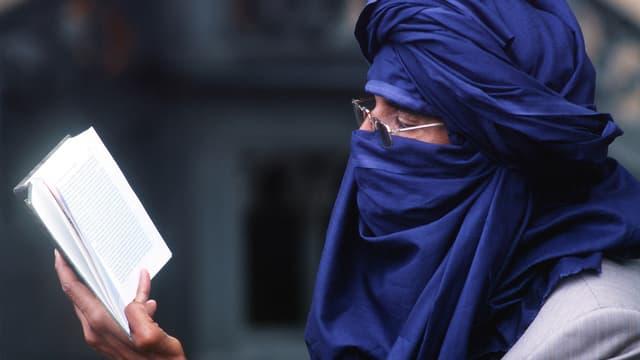 Ibrahim al-Konis Kopf ist in ein blaues Tuch gehüllt. Er liest. Man sieht ihn von der Seite.