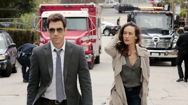 Ein Mann und eine Frau gehen eine Strasse entlang.