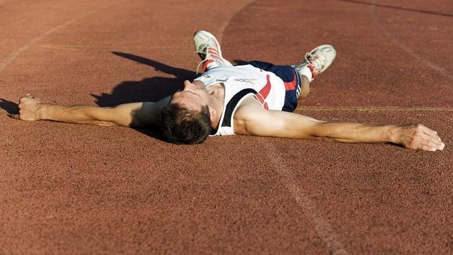 Sportler hat sich komplett verausgabt und liegt auf dem Rücken