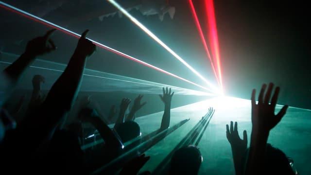 Junge Leute tanzen in einer Disco mit Lasershow.