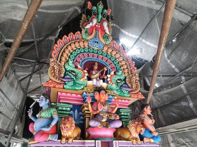 Spitze eines Hindutempels mit vielen farbigen Figuren.