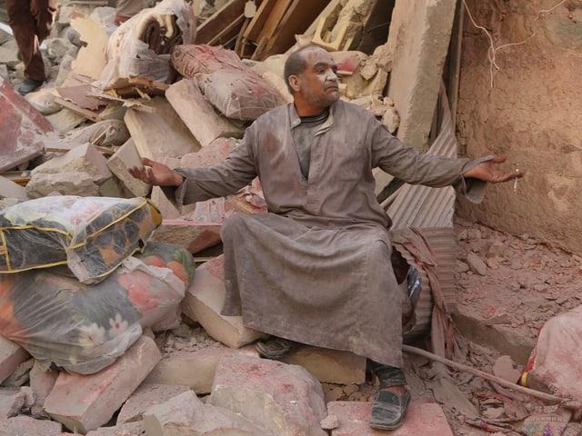 Ein Mann sitzt inmitten eines Trümmerhaufens und hebt die Hände gen Himmel.